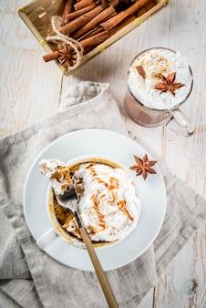 Receitas com abóboras, fast food, refeição de microondas. torta de abóbora picante em caneca, com chantilly, sorvete, canela, anis. na mesa de madeira branca, com uma xícara de chocolate quente. vista superior copyspace