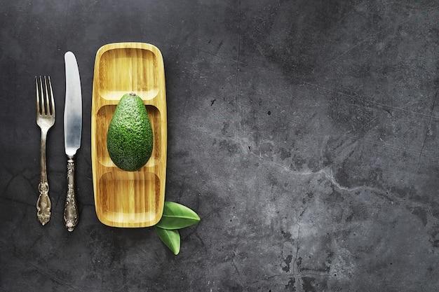 Receitas culinárias de abacate. abacate verde maduro em uma tábua de madeira para servir.