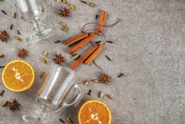 Receitas de bebidas quentes de natal conjunto de ingredientes para o vinho quente: duas xícaras de vidro temperam a laranja.