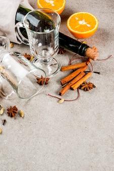 Receitas de bebidas quentes de natal, conjunto de ingredientes para vinho quente: garrafa de vinho, copos de vidro, especiarias, laranja, cópia espaço