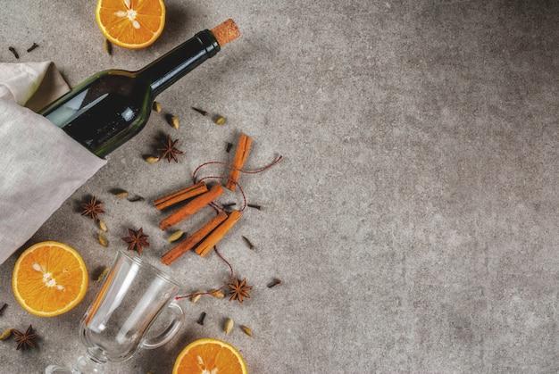 Receitas de bebidas quentes de natal, conjunto de ingredientes para vinho quente: garrafa de vinho, copos de vidro, especiarias, laranja