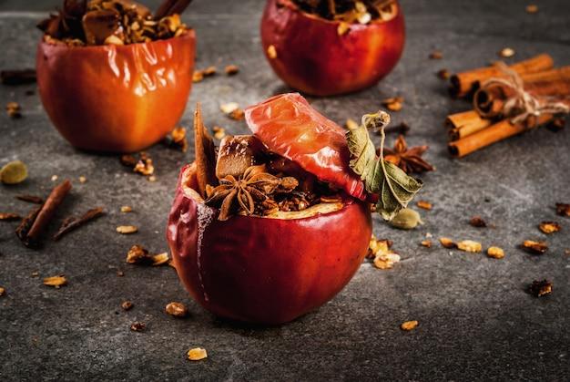 Receitas de comida de outono. maçãs assadas recheadas com granola, caramelo e especiarias. na mesa de pedra preta, copyspace