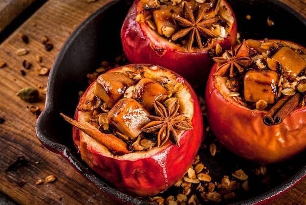 Receitas de comida de outono. maçãs assadas recheadas com granola, caramelo e especiarias. na mesa de pedra preta, na frigideira, copyspace