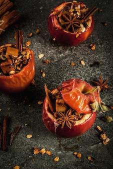 Receitas de comida de outono. maçãs assadas recheadas com granola, caramelo e especiarias. na mesa de pedra preta,