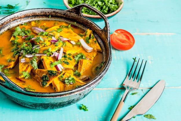 Receitas de comida indiana, omelete indiano masala egg curry, com legumes frescos - tomate, pimenta, salsa, fundo de madeira azul claro,