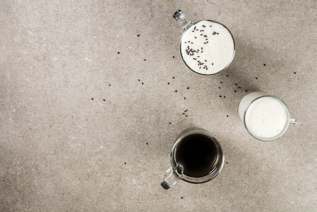 Receitas de comida vegan na moda, cappuccino de gergelim preto com sementes de gergelim e leite de coco batido, mesa de pedra cinza, vista superior copyspace