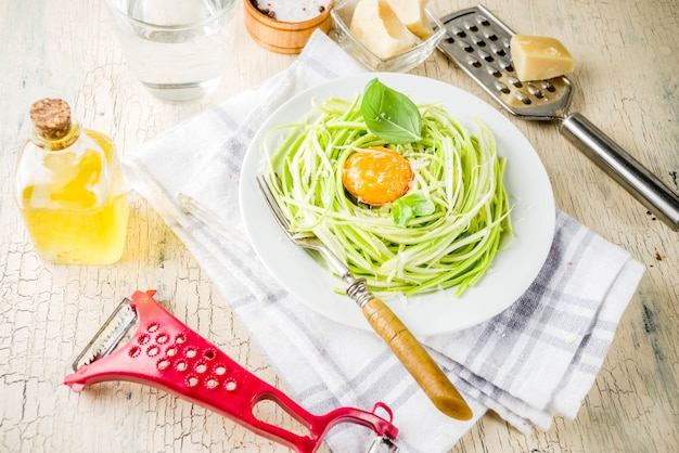 Receitas de comida vegan na moda, macarrão de espaguete de abobrinha de queijo com gema de ovo com parmesão, azeite e folhas de manjericão, espaço de cópia de luz de fundo concreto