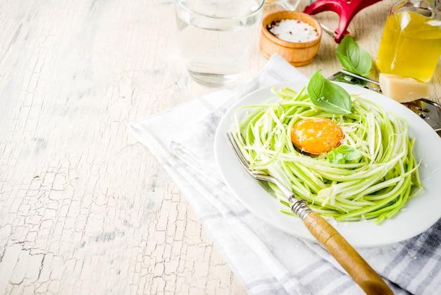Receitas de comida vegan na moda, macarrão de espaguete de abobrinha de queijo com gema de ovo com parmesão, azeite e folhas de manjericão, superfície de concreto leve