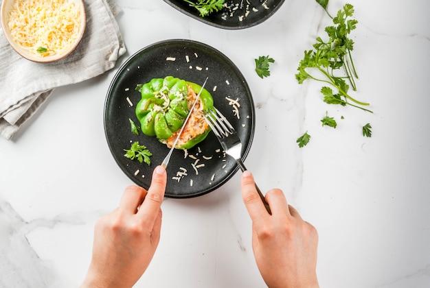 Receitas de outono. mulher come pimentão recheado caseiro com carne picada, cenoura, tomate, ervas, queijo. na mesa de mármore branca, em prato repartido, mãos na foto, vista superior do espaço de cópia