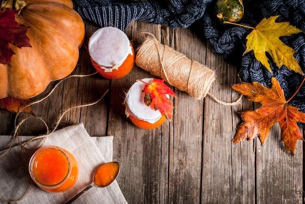 Receitas de outono, pratos de uma abóbora. doce de abóbora picante doce em uma jarra de servir, com uma colher, em uma velha mesa de madeira rústica decorada com abóboras, folhas de outono, um cobertor. espaço de cópia da vista superior