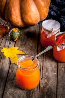 Receitas de outono pratos de uma abóbora doce de abóbora picante em uma jarra com uma colher em uma velha mesa de madeira rústica decorada com abóboras folhas de outono um cobertor
