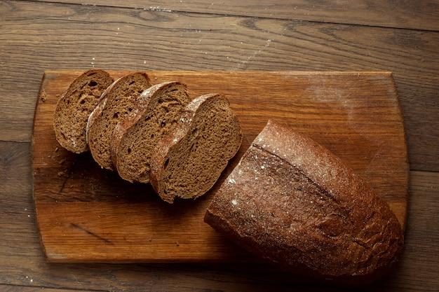Recém assado pão de centeio cortado em uma tábua de madeira