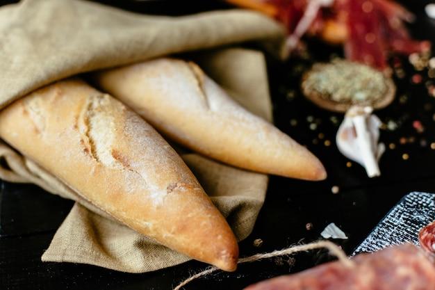 Recém-assados baguete francesa com iguarias de carne em uma mesa de piquenique