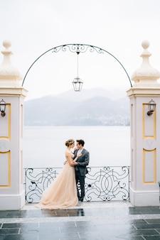 Recém-casados abraçados sob um arco antigo apoiado em uma cerca forjada