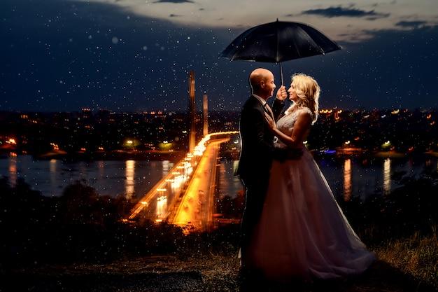 Recém-casados abraçando sob um guarda-chuva