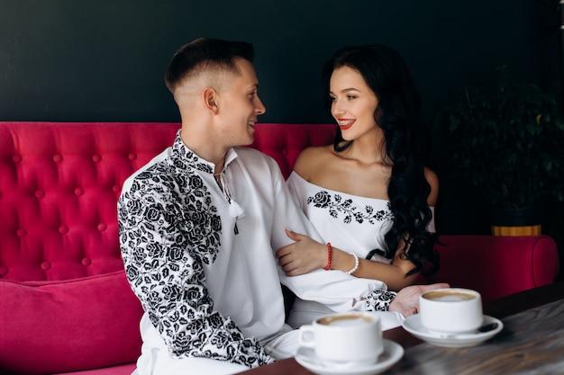 Recém-casados alegres descansar em um sofá cor-de-rosa brilhante no café