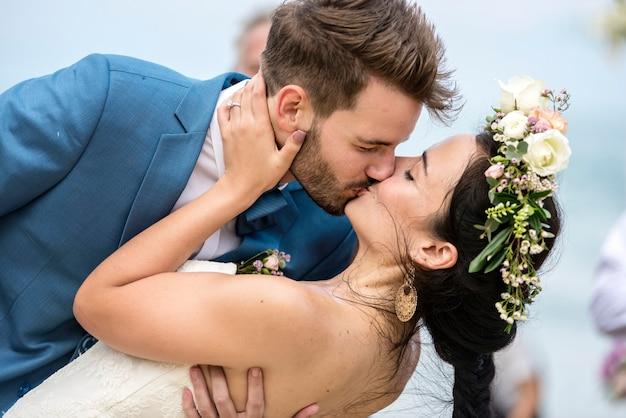 Recém-casados alegres no casamento de praia