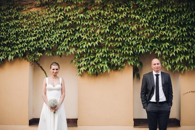 Recém-casados atraentes ficam juntos perto da parede do jardim