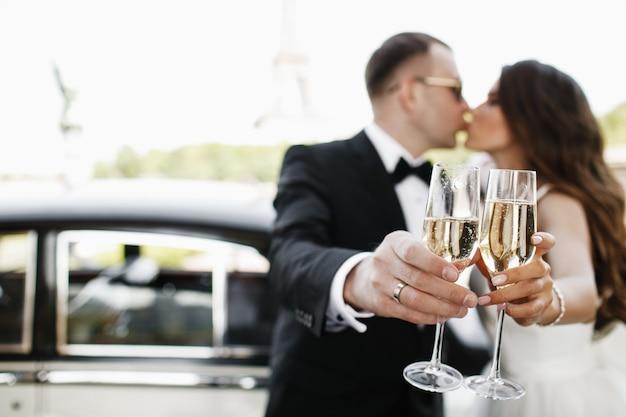Recém-casados bebem champanhe em pé diante de um carro retrô