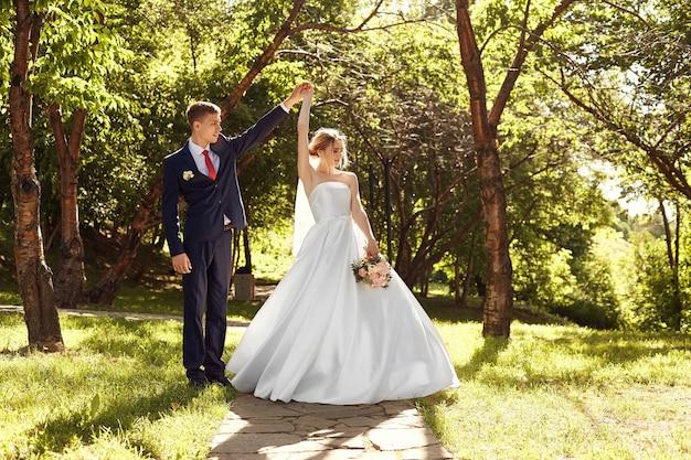 Recém-casados caminham na natureza no parque após a cerimônia de casamento. um beijo e um abraço de um homem e uma mulher. o noivo está segurando sua noiva