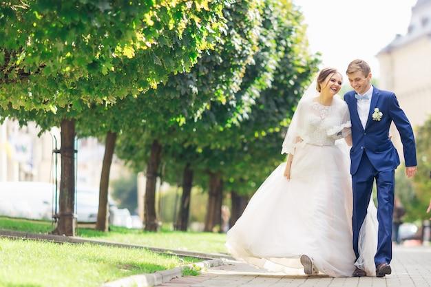 Recém-casados caminhando no parque e sorrindo sinceramente no dia do casamento
