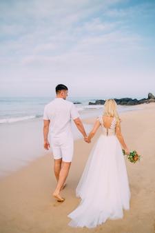 Recém-casados caminhando praia tropical, vista traseira