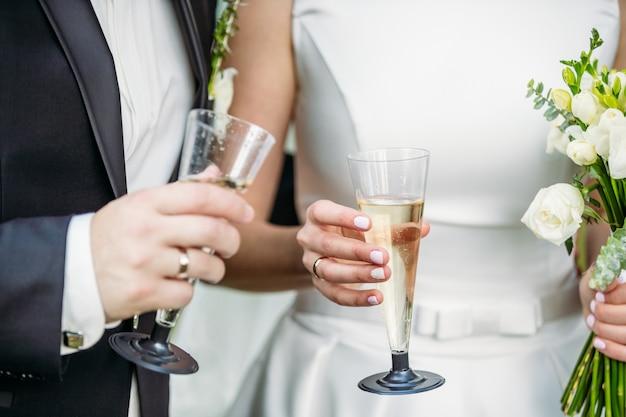 Recém-casados com champanhe em suas mãos