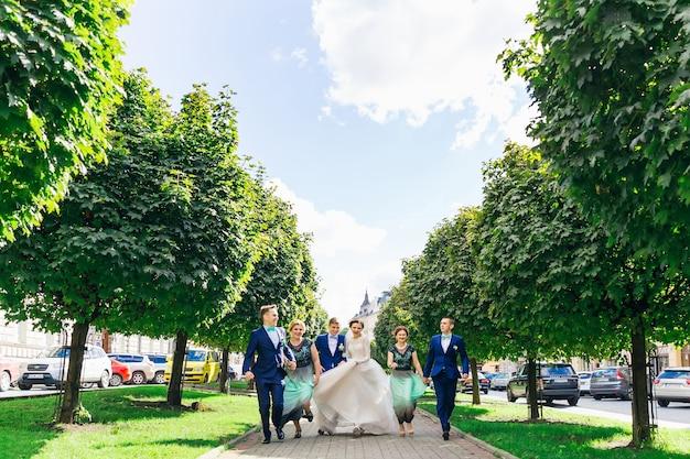 Recém-casados com damas de honra e padrinhos de mãos dadas e se divertindo no parque