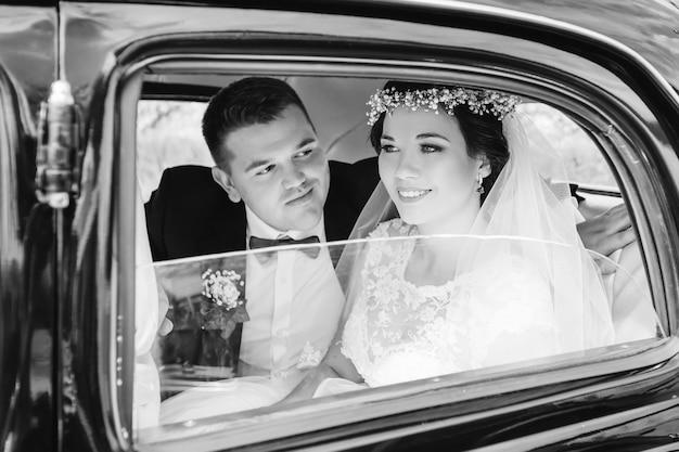 Recém-casados com roupas festivas sentados em um carro em fotos em preto e branco