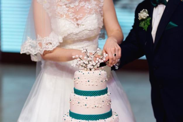 Recém-casados cortam um bolo de casamento segure a faca e corte o bolo de perto