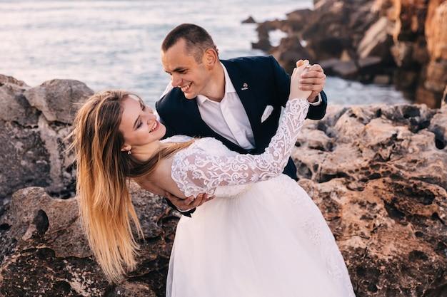 Recém-casados dançando na costa rochosa com vista para o mar