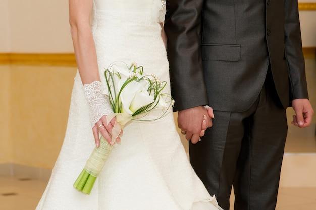 Recém-casados de mãos dadas. buquê de noiva luxuoso. cerimônia de casamento