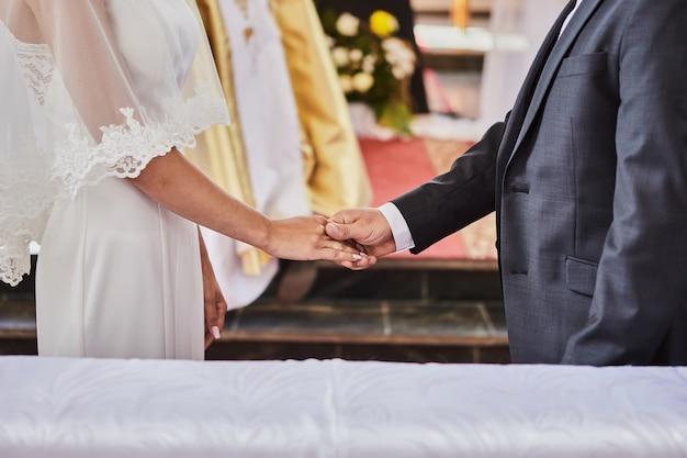 Recém-casados de mãos dadas durante um casamento em uma igreja católica
