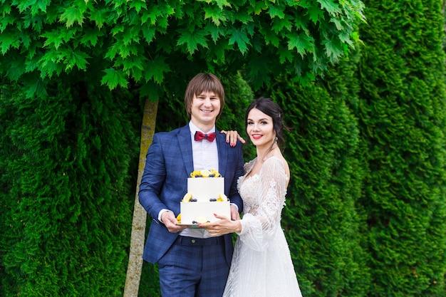 Recém-casados e damas de honra se divertem e comem bolo de casamento juntos ao ar livre em um banquete de casamento.