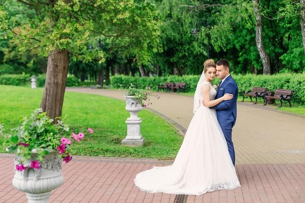 Recém-casados em roupas festivas, abraçando em um belo parque.