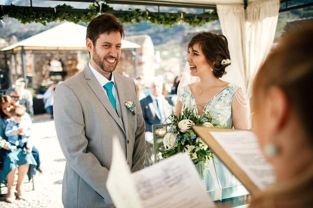 Recém-casados encantadores sorriam em pé diante de um altar de casamento