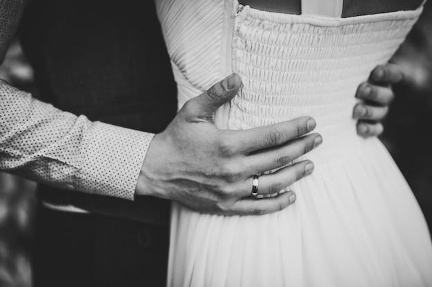 Recém-casados estão se abraçando. foto em preto e branco.