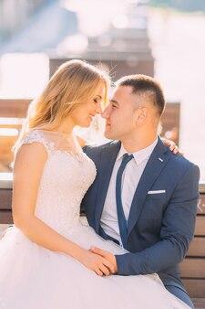 Recém-casados estão sentados em um banco com os olhos fechados e sorrindo