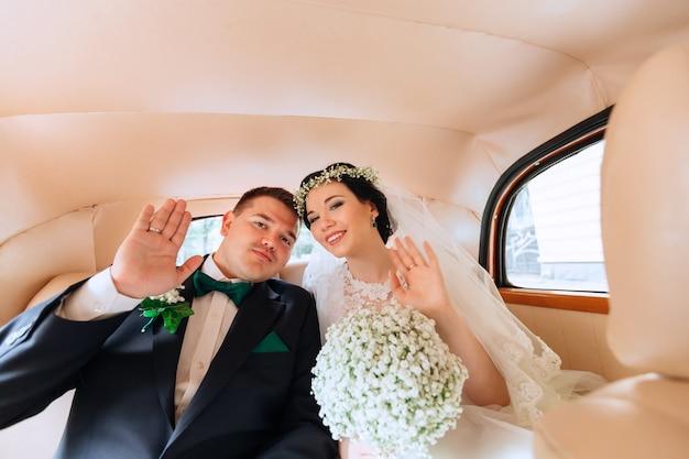 Recém-casados estão sentados no carro acenando com as mãos e olhando para o interior do carro