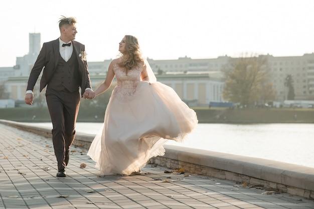 Recém-casados felizes correndo na calçada da cidade. foto com espaço de cópia