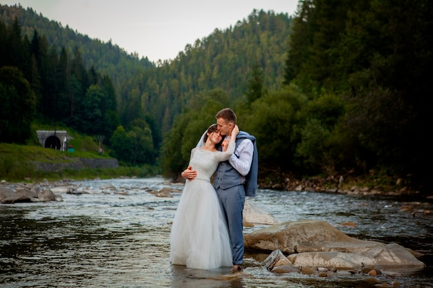 Recém-casados felizes em pé e sorrindo no rio.