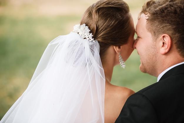Recém-casados felizes estão beijando e sorrindo. dia de casamento