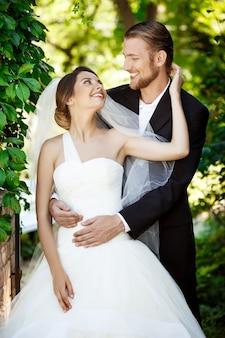 Recém-casados felizes sorrindo, olhando um ao outro no parque.