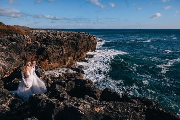 Recém-casados na costa rochosa do oceano