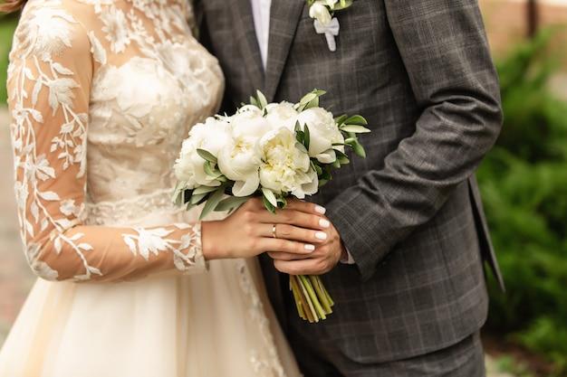 Recém-casados no dia do casamento, casal de noivos com buquê de flores, noiva e noivo