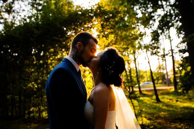 Recém-casados posando em um parque
