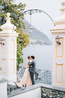 Recém-casados se abraçam e quase se beijam sob um antigo arco contra o pano de fundo do lago como