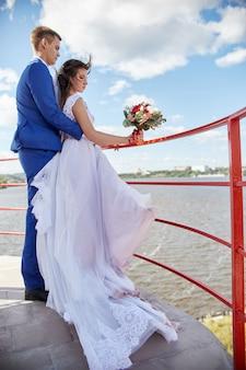 Recém-casados se abraçam e se beijam perto do farol no casamento