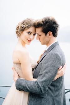 Recém-casados se abraçando contra o pano de fundo do lago como de perto