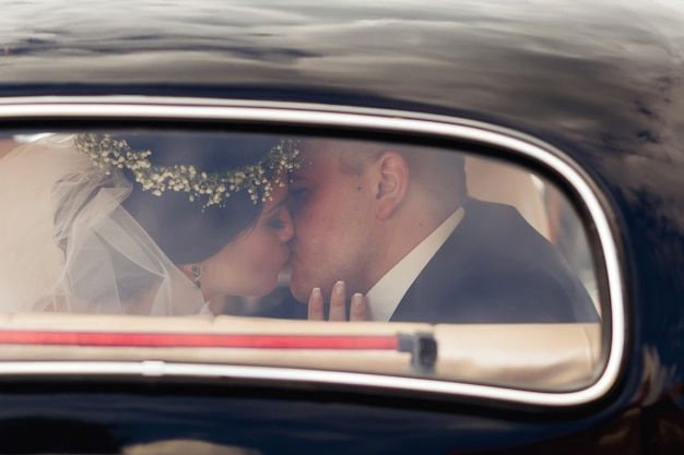 Recém-casados se beijando no carro os recém-casados são visíveis pela janela